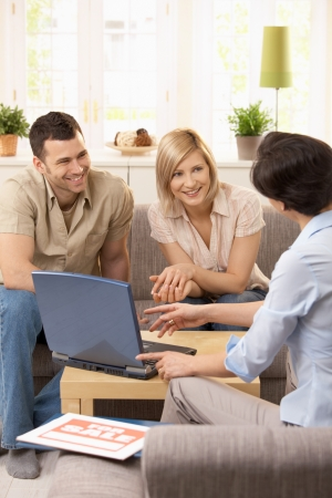 Young couple having appointment with estate agent in sunny living room. photo