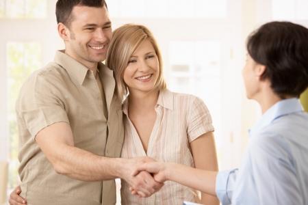 mani che si stringono: Coppia felice rendendo trattare con agente, sorridente uomo agitando le mani con agente.
