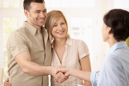 Happy couple making deal with agent, smiling man shaking hands with agent. photo
