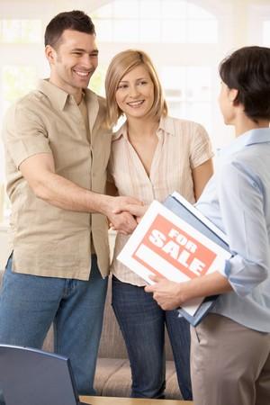 buen trato: Feliz pareja haciendo de acuerdo con el agente inmobiliario, agitando las manos.