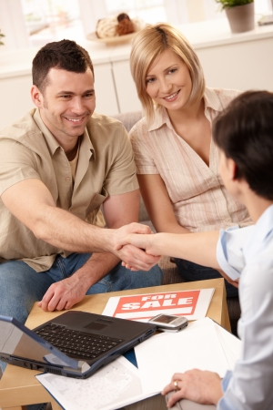 Estate agent shaking hand with young man, making deal with smiling couple in new house. Stock Photo