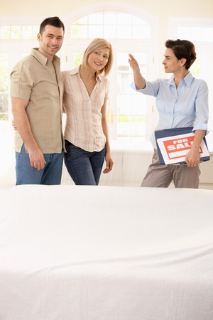 Estate agent showing young happy couple around in new house. Stock Photo - 7015718