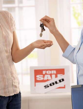 property agent: Estate agent handing over keys of new house to young owner. Stock Photo