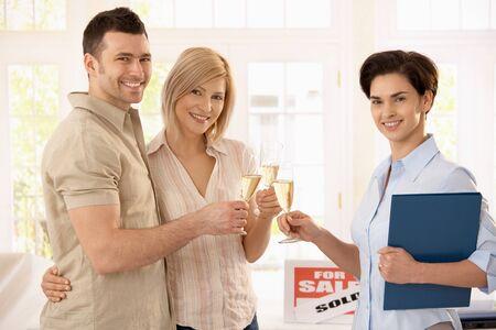 Makelaar paar champagne op de aankoop van nieuwe huis feliciteren.  Stockfoto
