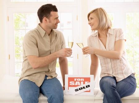 clinking: Joven pareja celebrando nuevos hogar, clinking champ�n gafas.