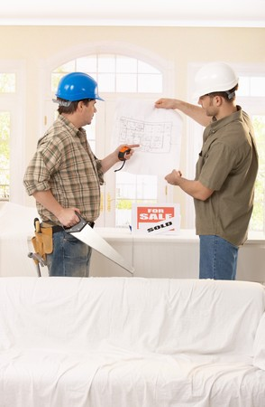 Builder pointing at ground plan, discussing project with architect. photo