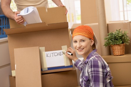 Man packing kitchen equipment into box, girlfriend signing box, smiling. photo