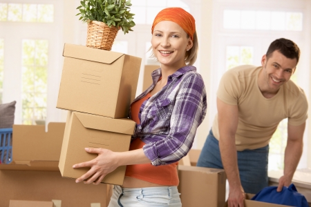 moving house: Happy couple carrying boxes at moving house.