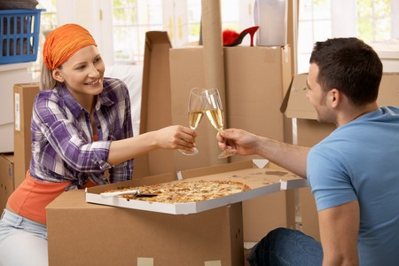 alcohol cardboard: Happy couple having pizza and champagne to celebrate moving house.