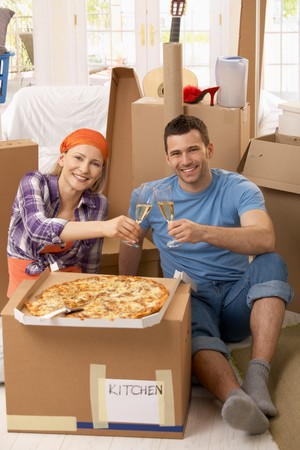 people celebrating: Happy couple celebrating new house with pizza and champagne at lunch break of moving.