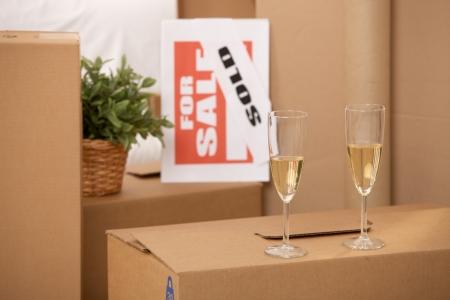 Celebrazione della nuova casa, due bicchieri di champagne, in piedi su un mucchio di caselle con segno di vendita.