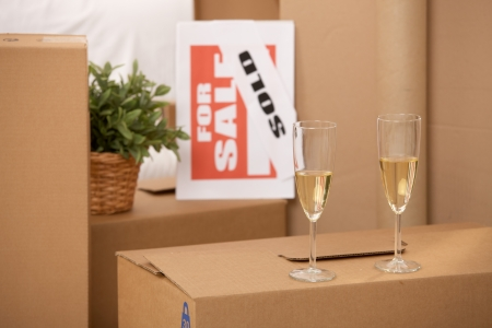 cardboard box: Celebration of new home, two champagne glasses standing on pile of boxes with for sale sign.