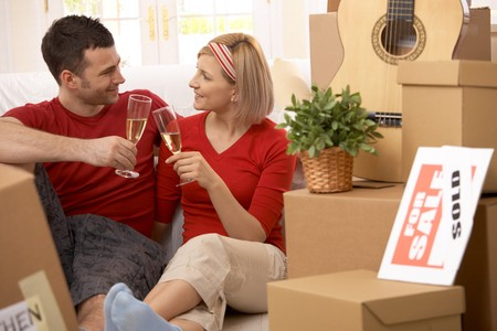 Happy couple celebrating moving to new house with champagne. photo