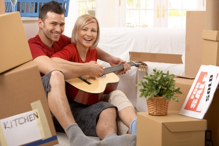 Happy couple playing guitar together in new house surrounded with boxes after moving. photo
