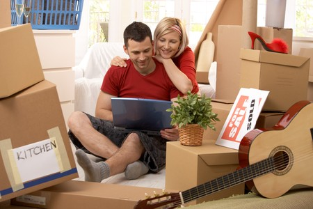 move: Happy couple looking at laptop computer together sitting in new house, surrounded with boxes.