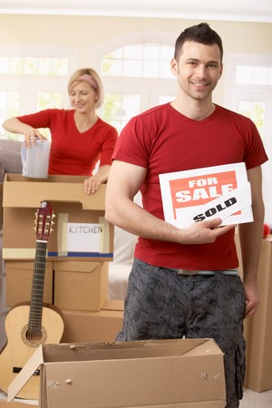 boxing day sale: Happy man in focus holding for sale sign changed to sold of new house, woman unpacking boxes in background.