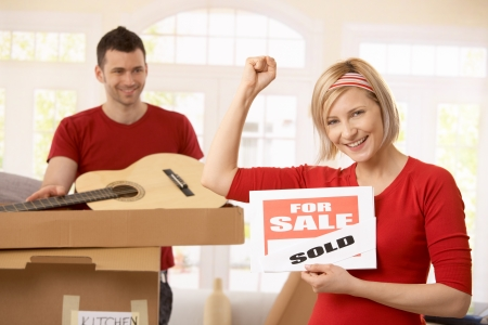 Smiling woman holding sold sign raising fist, happy man looking at her in background, unpacking boxes. photo
