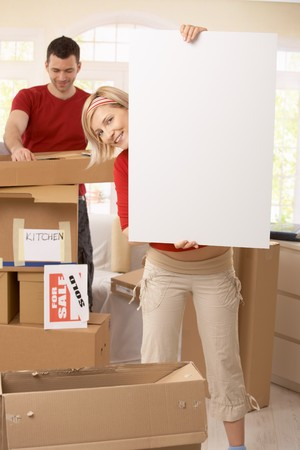 Happy couple moving into new place, copyspace in blank poster. photo