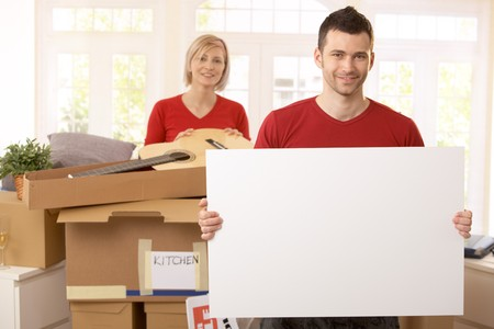 Smiling couple surrounded with boxes in new house, copyspace on blank poster. photo