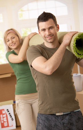 carrying girlfriend: Portrait of smiling couple moving place, carrying carpet on shoulder together. Stock Photo