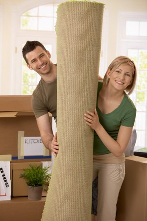 Portrait of smiling couple moving house, holding carpet rolled up, surrounded with boxes. photo