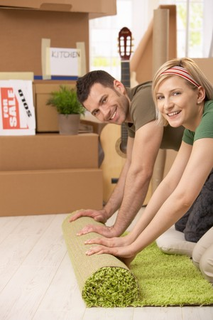 move: Portrait of smiling couple rolling out carpet together in new house.