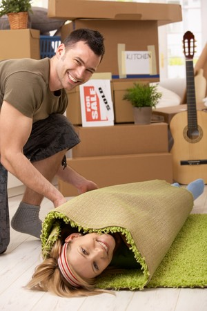 carpet color: Young couple having fun at moving house, laughing man rolling girlfriend into carpet. Stock Photo