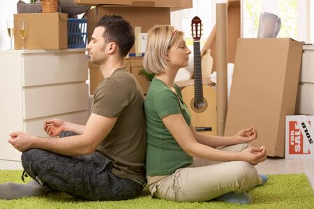 Young couple sitting in yoga meditation posture on carpet in new house, surrounded with boxes. photo