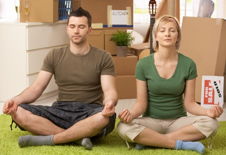 two floors: Young couple doing yoga meditation in new house after moving, sitting in middle of boxes.