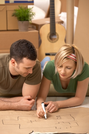 new home: Young couple lying on floor of new house planning home together on paper.
