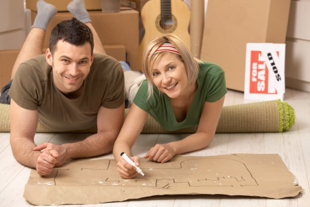 lying in front: Portrait of smiling couple lying on floor of new house making plan to furniture their home together on paper. Stock Photo