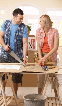 Happy couple improving new house, working together at table. photo