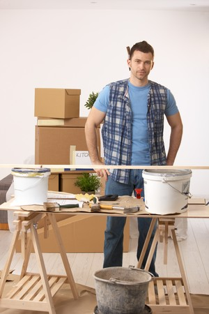 Portrait of young man standing at table in new house, preparing to paint walls. photo