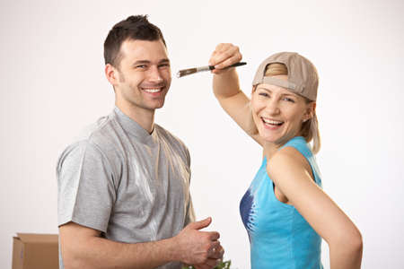 Portrait of happy couple painting together, laughing. photo