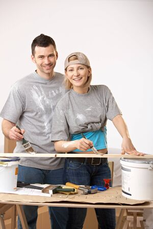 Happy couple working on their new home together, painting at table. Stock Photo - 7015870