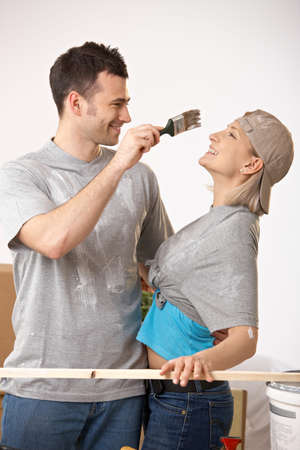 Young couple having fun at painting house, man trying to paint girlfriend nose. photo