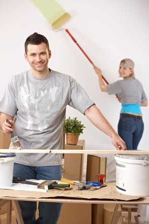 Cheerful young man painting stave at table, girlfriend painting wall in background. photo