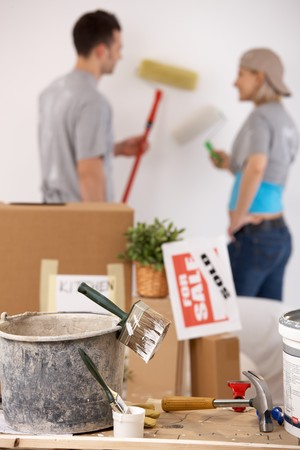 Young couple painting their new house with paint roller, equipment in focus. photo