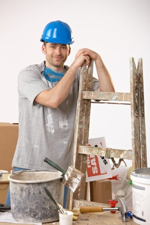 Portrait of young smiling guy surrounded with painting equipment. photo