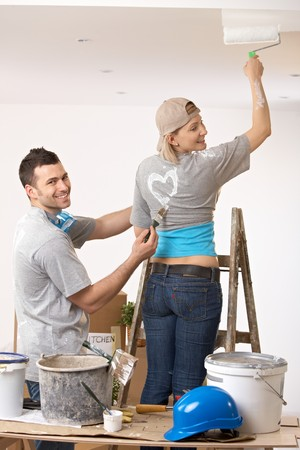 Smiling woman painting the ceiling standing on ladder, laughing guy painting heart on tshirt. photo