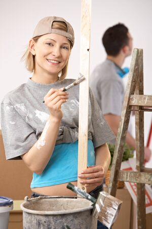 Portrait of smiling woman painting, working on new house, boyfriend standing in background. photo