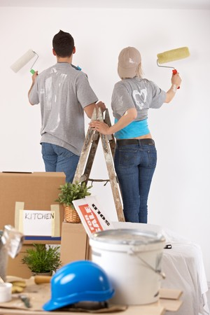 Couple standing on one ladder, painting wall together with paint roller. photo