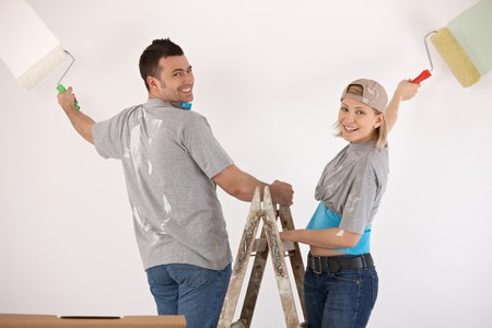 Portrait of smiling couple standing on ladder, painting wall together with paint roller. photo
