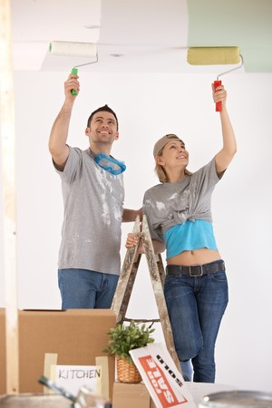 Portrait of smiling couple standing on ladder, painting ceiling of new home with paint roller. photo