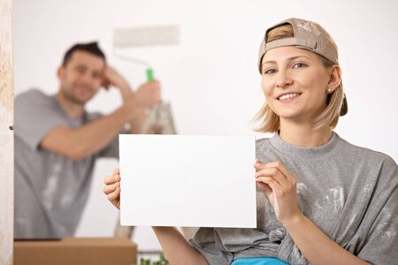 Smiling couple painting new house, woman in focus holding blank page, copyspace. photo