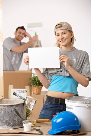 Smiling couple painting new house, blank page for copyspace. Stock Photo - 7015854