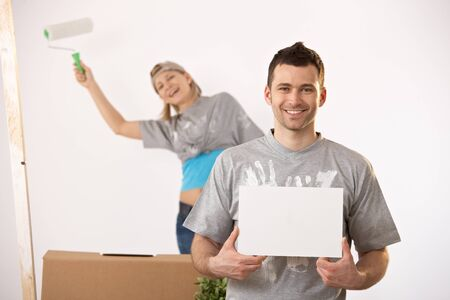 Happy couple painting new house together, smiling man holding blank page for copyspace. photo
