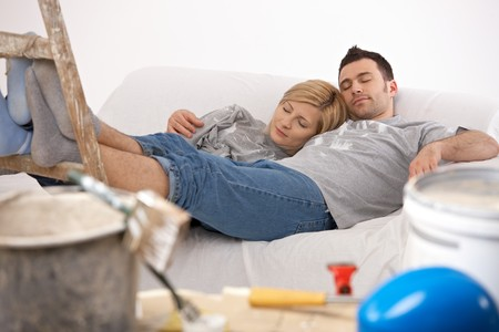 Couple lying together after painting with closed eyes, relaxing after hard work with feet up on ladder. photo