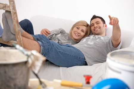 after work: Smiling couple lying together after painting, man pointing at funny detail, woman laughing. Stock Photo