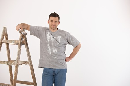 Portrait of handsome guy with paint brush and ladder, looking at camera, smiling. photo